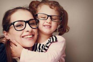 happy mother and daughter wearing glasses